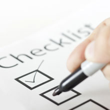 Checklist with a person using a black marker to check the boxes.